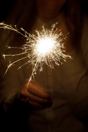 Amazing sparklers in female hands. Christmas and new year bengal lights in hand toning.