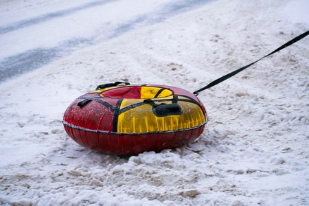 Empty snow tubing in the road. Yellow and red snow tubing.