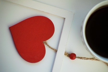 Cup of love, coffee with red heart. Red heart on a rope in the wooden frame. Valentines day. Morning. The 14th of February. Stock Photo