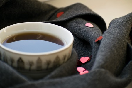 Cozy soft gray scarf with a cup of coffee. The mug is wrapped in a knitted scarf. The 14th of February. Imagens - 93989167
