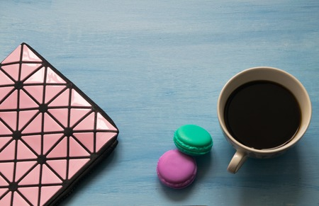 Cosmetic bag, cup of coffee, macaroons on blue background