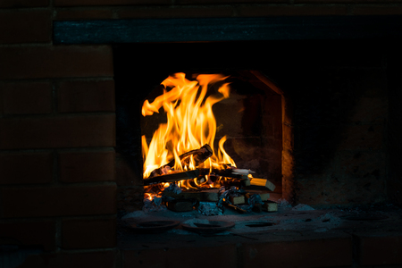 Crest of flame on burning wood in fireplace. Stock Photo