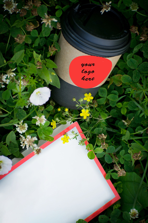 Brown paper glass with black lid for coffee on green grass. Cup of coffee with book on the grass.