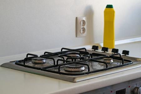 Estufa de gas muy sucia. Limpiar la estufa de gas con un agente limpiador.