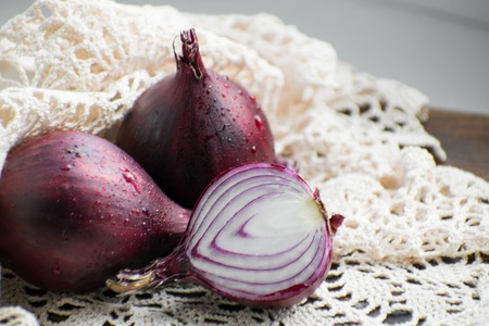 Red onion and red onion slices on wooden cutting board. Banco de Imagens - 108376405