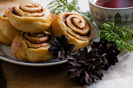 Cinnamon rolls buns with spices . Cinnamon cookie with tea on christmas background