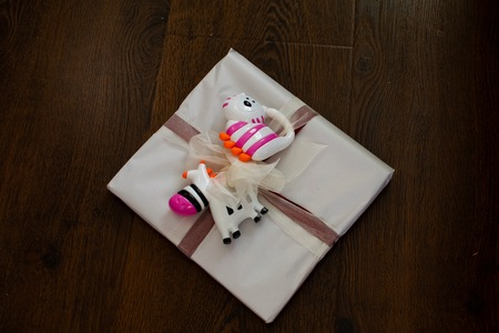 Gift tied with a bow for a newborn with rattles Gift for newborn, birthday. Bright rattles for baby.