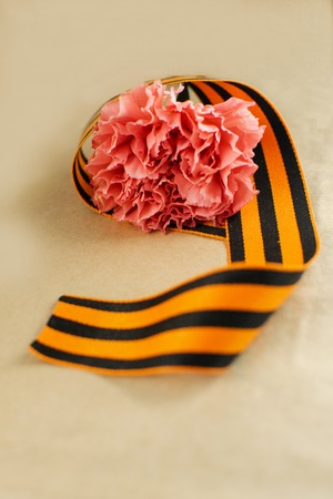 Carnation and St. George ribbon on craft background, symbol of the great Victory, victory day, 9 May background
