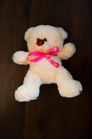 Cute teddy bear on wooden background. Fluffy teddy bear with a pink bow. A gift to the child for the holiday. Valentine's Day Gift.