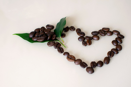 Shiny fresh roasted coffee beans with green leaf in the shape of a heart on light background.