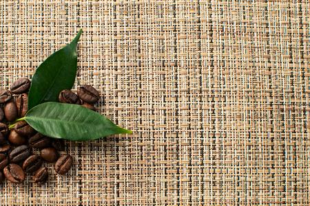 Shiny fresh roasted arabica coffee beans with green leaf on brown background 版權商用圖片