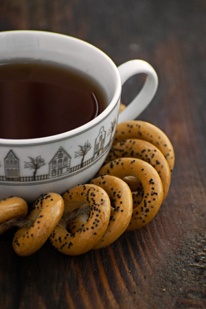 Traditional russian bagels with cup of tea on a wooden board.