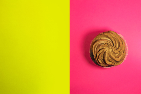 Beautiful hoemade chocolate cupcake with butter cream and cocoa on yellow and pink background.