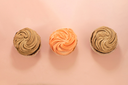Beautiful homemade strawberry and chocolate cupcake with butter on pink background.