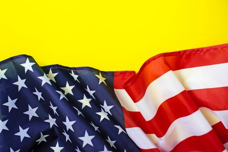 Closeup of American flag on bright yellow background.
