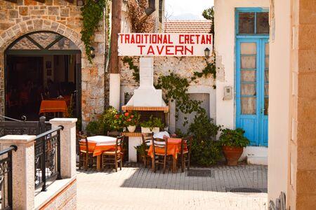 Traditional greek outdoor restaurant on terrace, empty table at an street village restaurant, Crete, Greece. Banco de Imagens