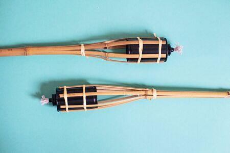 Un gros plan de la lampe à huile de torches en bambou traditionnel malais sur fond bleu. Banque d'images