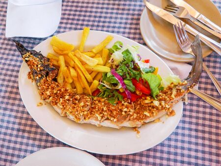 Baked shark with garlic, vegetables and french fries. Breakfast in an Indian cafe.