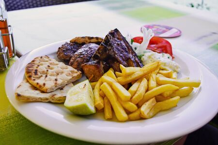 Greek Gyros with fries and vegetables and tzatziki sauce, Traditional turkish, greek meat food. Фото со стока