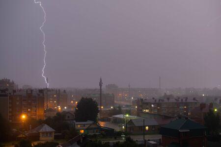Hermoso y poderoso rayo sobre el cielo gris oscuro en la ciudad de noche. Foto de archivo