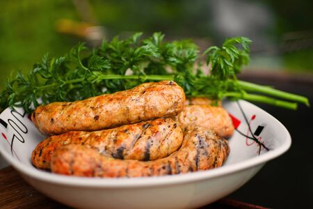 Appetizing grilled bavarian sausages on a white plate with parsley and dill.