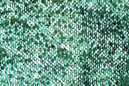 Texture of neo mint shiny sequins. Fashionable bright fabric with sequins.
