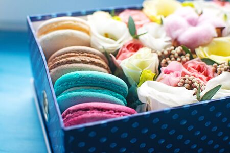 Blue box of tender flowers and bright macarons. Romantic gift for your beloved woman. Selective focus.