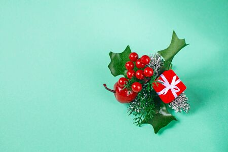 Red christmas box with spruce twig, apple and berries on a mint background.