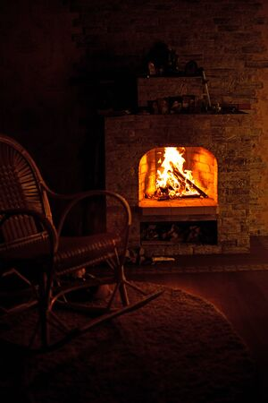 Rocking chair by the fireplace in a rustic house. Cozy evening by the fireplace.