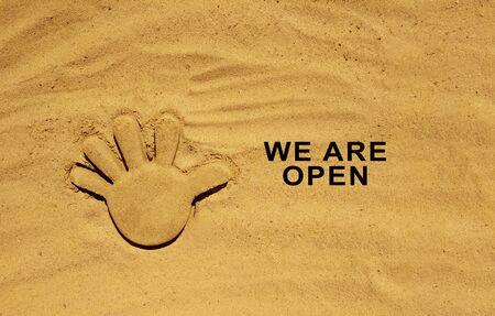 End of quarantine. Text message W are open on the sand. Welcome sign on the beach. Hotel, cafe, beach, travel service owner welcoming guests after coronavirus outbreak. Zdjęcie Seryjne