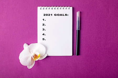 Open notebook with orchid and marker with new year goals words on violet background. Planning concept.