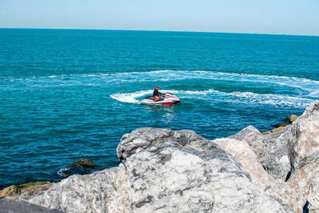 Dubai, United Arab Emirates January 16, 2020: Man riding jet ski in in Persian Gulf, Dubai. Tourist enjoy driving jetski on the ocean.
