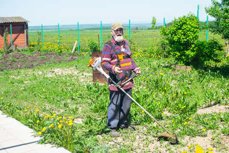 Elderly man mows grass in his house with an electric trimmer. Taking care of garden.
