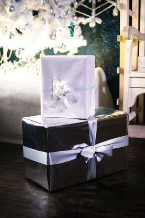New Years and Christmas gift boxs under the fir-tree. Holiday greeting card.