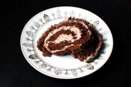 Swiss sponge cake with cream and chocolate on a white plate.