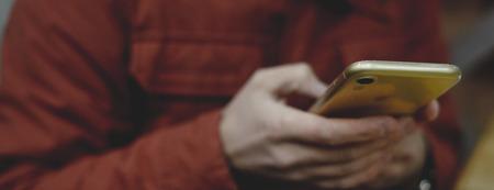 Close up of a man using mobile smart phone, orange color