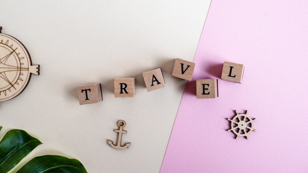 Wooden sign text TRAVEL on pink and yellow background. Flat lay. Summer, vacation, holidays concept. Banner Фото со стока