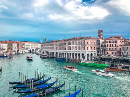 Venice, Italy - Mart 2019: Aerial view of Rialto Market with gondola passing from Grand Canal Editoriali