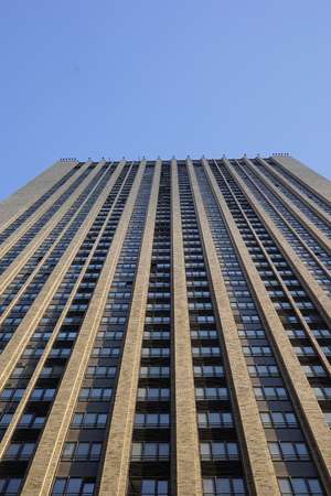 Vertical view of a tall concrete modern high building with geometric details against a blue sky