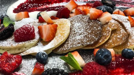 Homemade pancakes serving with fresh raspberry, blueberry, strawberry, with sauce and pondered sugar, selective focus, banner