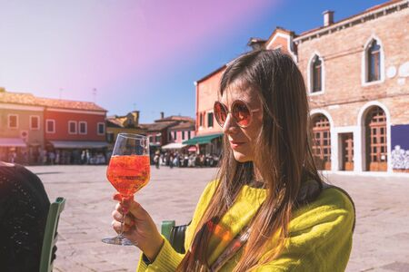 Young woman in yellow jacker with glass of aperol sitting on square in sunny day. Burano, Venice, Italy.