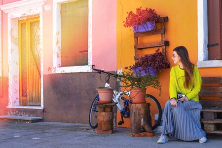 Young woman in yellow jacker with professional camera sitting on square in sunny day. Burano, Venice, Italy.
