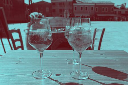 Duotone image, dark and cyan blue. three glasses of fresh drinks with architecture reflections. Venice Italy. 스톡 콘텐츠