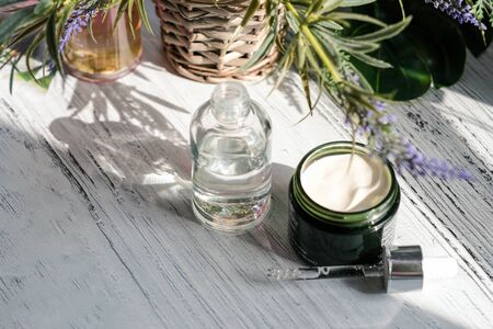 Cosmetic cream container and a bootle of serum with green herbal leaves on white table Stock Photo