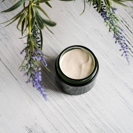 Cosmetic cream container with green herbal leaves on white background