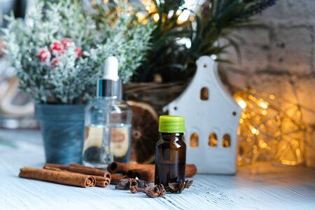 Relaxing winter season Essential oils blend. Dark glass bottles, cinnamon, orange, pine twigs, anise.