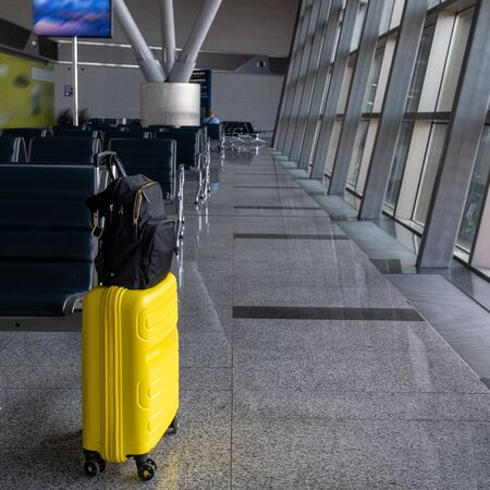 Travel yellow suitcase with black backpack at the empty airport