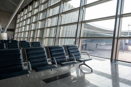 There are empty chairs, benches for passengers waiting for flights at the airport terminal, selected focus