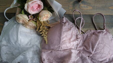 Woman elegant pink and white lace bras, flowers, jewelry. Stylish lingerie flat lay. Underwear fashion concept