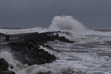 waves hitting against the pier during storm in Nr. Vorupoer on the North Sea coast in Denmark